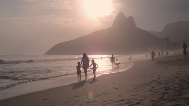 MS A woman walks along the beach with two children at sunset / Rio de Janeiro, Brazil