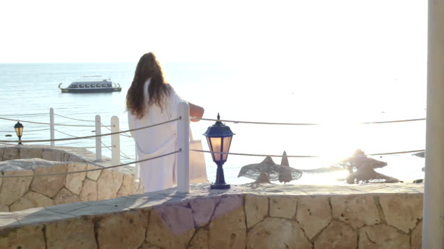 a woman walks along the promenade of a tourist hotel in egypt. - red sea stock videos & royalty-free footage