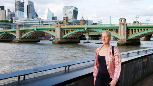 woman walks along the thames river embankment with the southwark bridge behind her in london, england. - naga river stock videos and b-roll footage