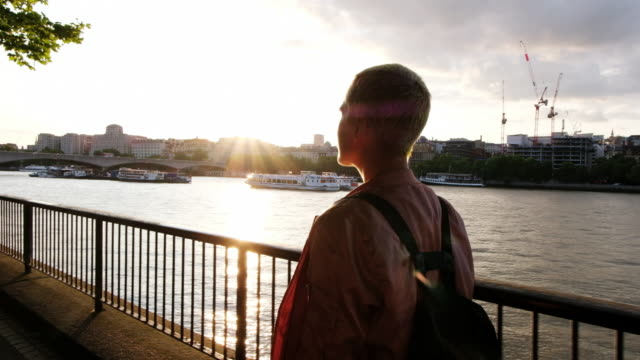 woman walks along the thames river in london, england during sunset. - naga river stock videos and b-roll footage