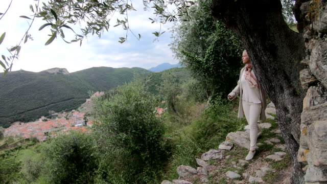woman walks along track through olive grove - leggings stock videos & royalty-free footage