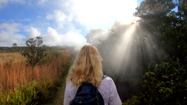 woman walks along volcanic path, wearing backpack - blonde hair stock videos & royalty-free footage