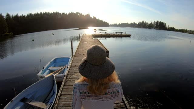 woman walks along wooden lake pier at sunrise - pier stock videos & royalty-free footage