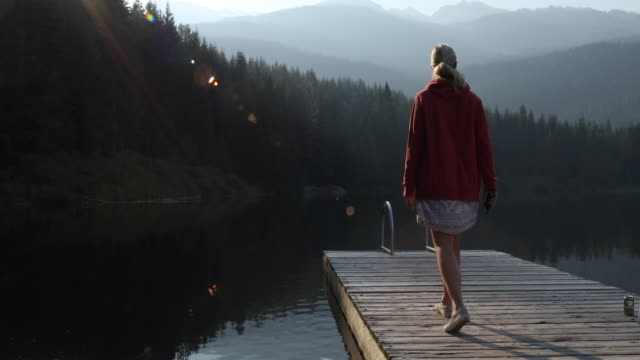 stockvideo's en b-roll-footage met woman walks along wooden pier, touches water surface - alleen één oudere vrouw