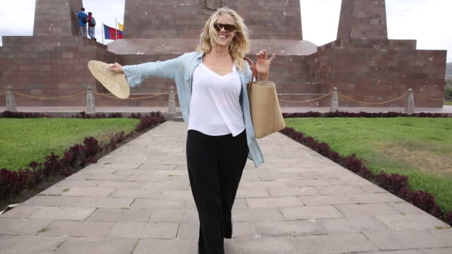 Woman walks along zero line from Monument to the Equator