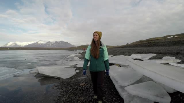 女性は氷河湖で、黒い砂のビーチの氷山の間で歩く - トラッキングショット点の映像素材/bロール