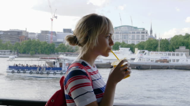 woman walks at river embankment, drinking fruit juice. - on the move stock videos & royalty-free footage
