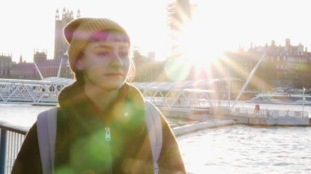 woman walks at river embankment in winter sunlight, slow-motion. - turismo urbano video stock e b–roll