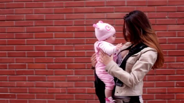 woman walks at the street keeping her baby on hands - okänt kön bildbanksvideor och videomaterial från bakom kulisserna
