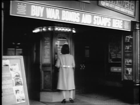 B/W 1943/44 woman walks away from ticket booth at movie theater with war bonds sign / NJ / newsreel