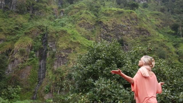 woman walks below rainforest cliff, waterfall - blonde hair stock videos & royalty-free footage