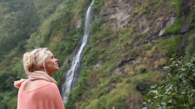woman walks below rainforest cliff, waterfall - tunic stock videos & royalty-free footage