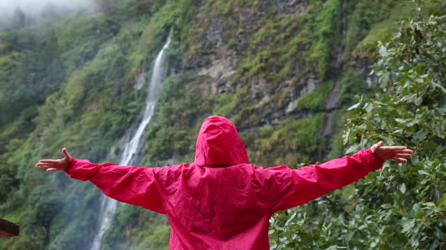 vídeos de stock, filmes e b-roll de woman walks below rainforest waterfall, in mist - capa de chuva