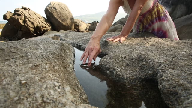 Woman walks between boulders, stroking water with hand