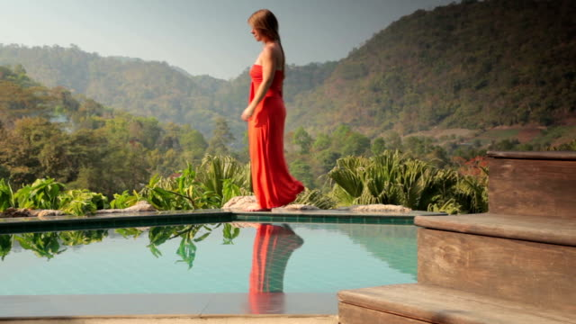 Woman Walks by a Private Swimming Pool on Vacation