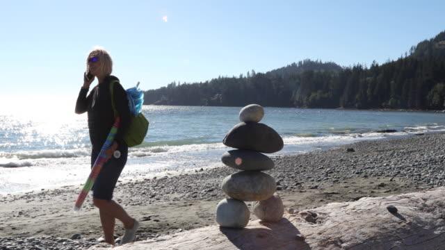 woman walks by inukshuk on log, talking on smart phone - indigenous culture stock videos & royalty-free footage