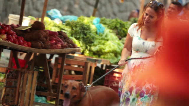 Woman walks dog through bustling outdoor farmers market