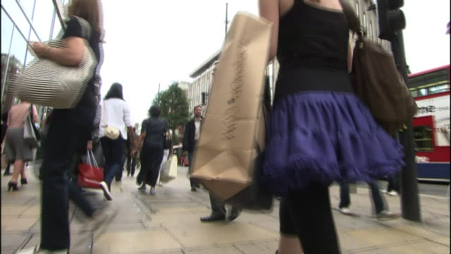 A woman walks down a street with a shopping bag.