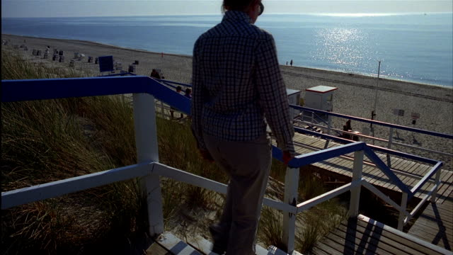 a woman walks down stairs to a beach on north sea. island of sylt, schleswig-holstein, germany - nordfriesische inseln stock-videos und b-roll-filmmaterial