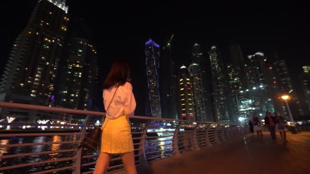 woman walks down street in dubai at night - nightlife stock videos & royalty-free footage
