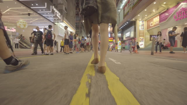 vídeos y material grabado en eventos de stock de woman walks down street in hong kong, low angle - toma en travelling