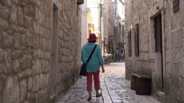 vídeos y material grabado en eventos de stock de a woman walks in an alley with stone houses in old town - cultura croata