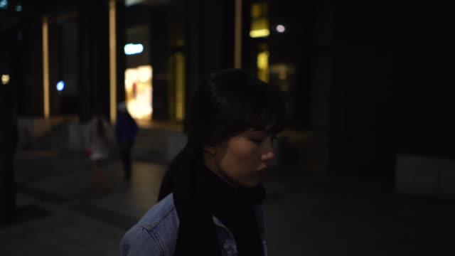 vídeos de stock, filmes e b-roll de woman walks in downtown seoul at night, tracking shot - neckwear