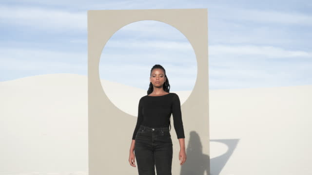 woman walks in front of placard with circle window frame in desert, - jeans bildbanksvideor och videomaterial från bakom kulisserna