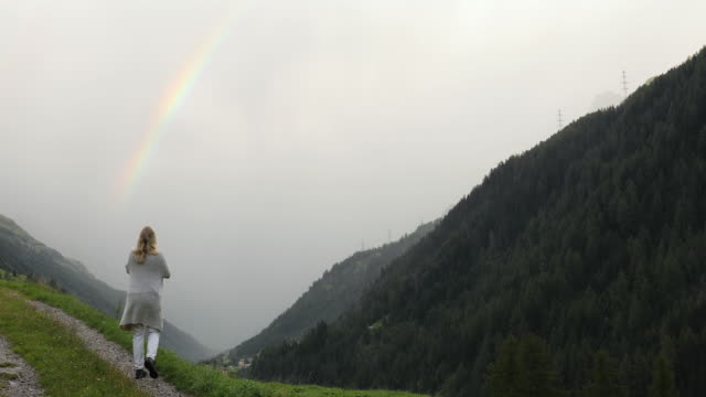 woman walks into alpine meadow, takes pic of rainbow - langes haar stock-videos und b-roll-filmmaterial