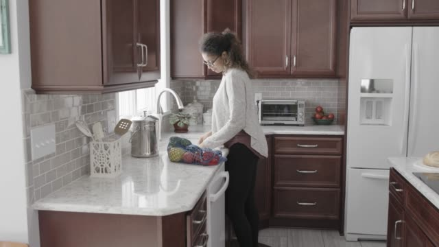 vídeos de stock, filmes e b-roll de woman walks into kitchen and washes vegetables - só uma mulher de idade mediana