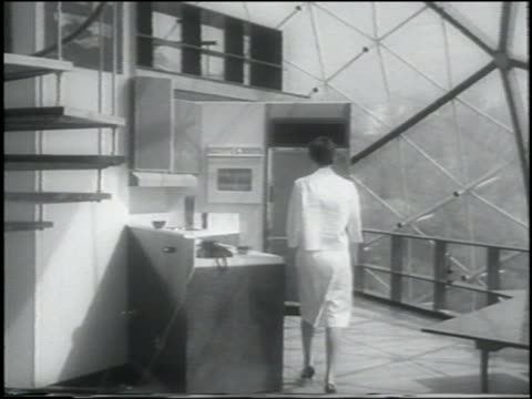 B/W 1962 woman walks into kitchen in futuristic geodesic dome house