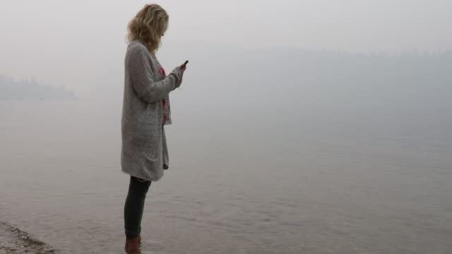 Woman walks into lake shallows on foggy day, distant hills visible