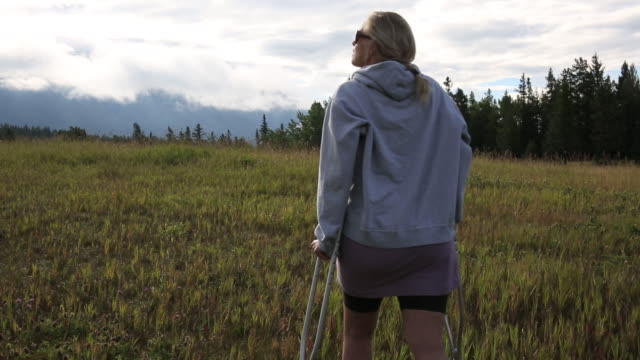 Woman walks into meadow on crutches, looks out across mountains