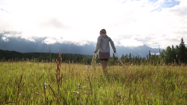 woman walks into meadow on crutches, looks out across mountains - crutch stock videos & royalty-free footage