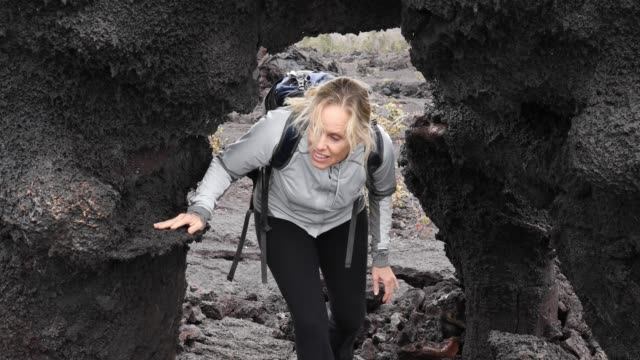 女性は、バックパックを身に着けている火山の風景に歩く