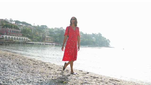 a woman walks on a beach in a red dress while traveling in a luxury resort town in italy, europe. - slow motion - sandal stock videos & royalty-free footage