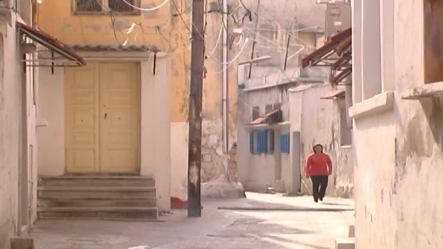 woman walks on a narrow street in a christian quarter of tyre. tyre in southern lebanon is an ancient city with important archaeological remains. - christianity stock videos & royalty-free footage