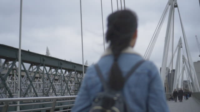 woman walks on bridge, london - looking around stock videos and b-roll footage