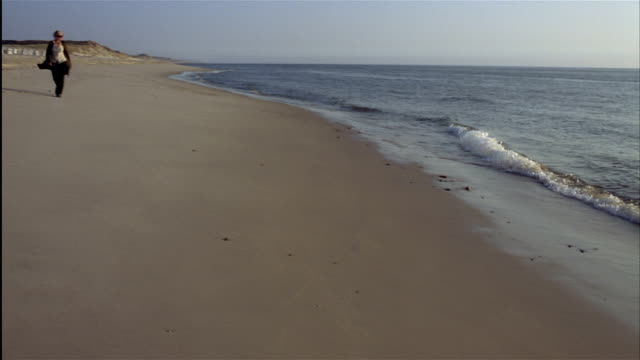 wide pan woman walks on deserted beach - sylt stock videos & royalty-free footage