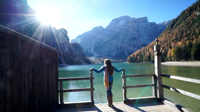woman walks on dock to lookout over alpine lake - trentino alto adige südtirol video stock e b–roll