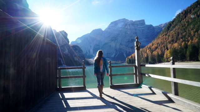 Woman walks on dock to lookout over alpine lake