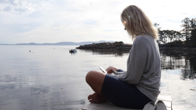 woman walks on pier above tidal lagoon, sunrise - tee stock videos & royalty-free footage