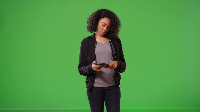 Woman walks on screen checks her mobile phone then exits off on greenscreen