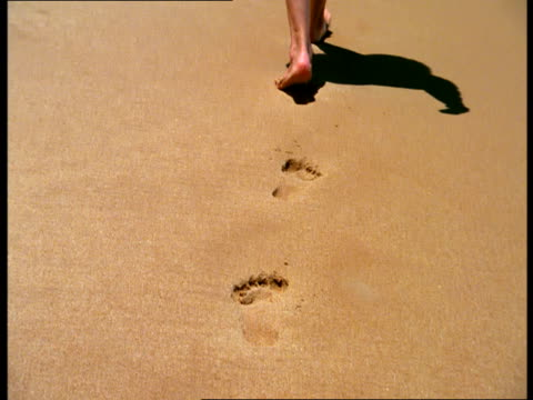 A woman walks on the beach, leaving footprints in the sand.