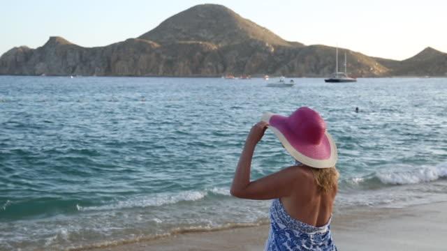 vídeos y material grabado en eventos de stock de woman walks onto beach, looking out to sea - rosa brillante