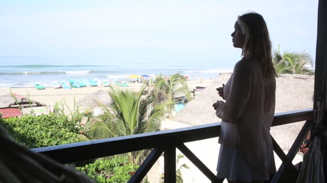 Woman walks onto beachside terrace, looks out