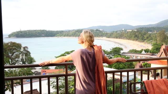 woman walks onto deck above beach, looks out across lagoon - プーケット県点の映像素材/bロール