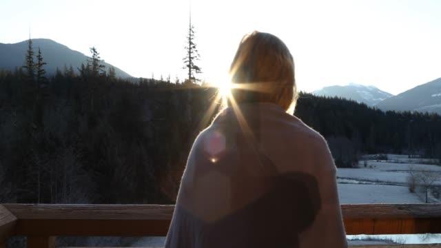 frau geht bei sonnenaufgang über berge auf deck - eingewickelt stock-videos und b-roll-filmmaterial