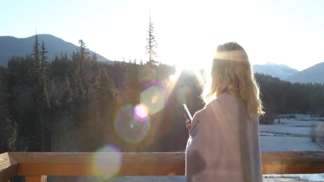 woman walks onto deck at sunrise, above mountains - see other clips from this shoot 56 stock videos & royalty-free footage