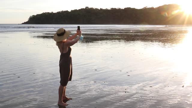 vídeos y material grabado en eventos de stock de woman walks onto empty beach, takes smart phone pic - photographing